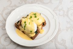 Eggs Benedict for brunch. Close up of poacheg eggs with bacon, shpinach and hollandaise sause royalty free stock photo