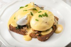 Eggs Benedict for brunch. Close up of poacheg eggs with bacon, shpinach and hollandaise sause stock image