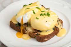 Eggs Benedict for brunch. Close up of poacheg eggs with bacon, shpinach and hollandaise sause stock images