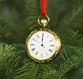 Close up of pocket watch on conifer branch with red lace. Vintage pocket watch hanging on natural conifer branches. Christmas and New Year card with copy space stock photography