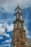 Close-up of pointed bell tower church made of bricks and golden clock under blue sky in Amsterdam. The city is famous for its huge cultural activity, graceful Royalty Free Stock Images