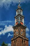 Close-up of pointed bell tower church made of bricks and golden clock under blue sky in Amsterdam. The city is famous for its huge cultural activity, graceful Royalty Free Stock Image