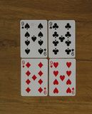 Poker cards on a wooden backround, set of nines of clubs, diamonds, spades, and hearts royalty free stock photos