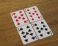 Poker cards on a wooden backround, set of nines of clubs, diamonds, spades, and hearts royalty free stock photo