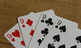 Poker cards on a wooden backround, set of nines of clubs, diamonds, spades, and hearts royalty free stock image