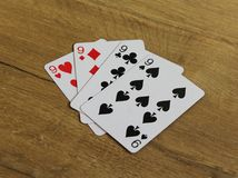 Poker cards on a wooden backround, set of nines of clubs, diamonds, spades, and hearts royalty free stock images