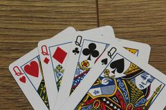 Poker cards on a wooden backround, set of queens of clubs, diamonds, spades, and hearts royalty free stock image