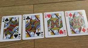 Poker cards on a wooden backround, set of queens of clubs, diamonds, spades, and hearts royalty free stock photography
