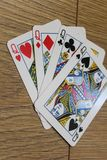 Poker cards on a wooden backround, set of queens of clubs, diamonds, spades, and hearts royalty free stock images