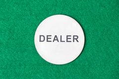Close up of poker dealer chip on the green table Royalty Free Stock Photo