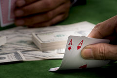 close up of poker player with cards and money sheet at green casino table royalty free stock photo