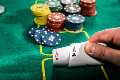 Close up of poker player with two aces playing cards and chips at green casino table Stock Photos
