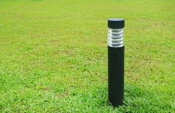 Close up pole of lamp in green grass field. royalty free stock image