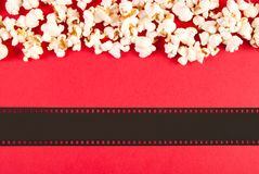 Close up popcorn and film tape on red background, top view and space for text. Popcorn and film tape isolated on red background. Empty space for text and design Royalty Free Stock Images