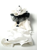Close up of porcelain clown doll. Close up of white porcelain clown doll dressed in white robe with black accents seated on white Royalty Free Stock Image