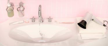Close-up of porcelain washbasin in pink bathroom. Set for mornin. G hygiene. Toothpaste, brushes, soap, hairdryer and towel Stock Images