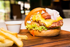 Close up on Pork burger with cheese, vegetable and served with fries Royalty Free Stock Photography