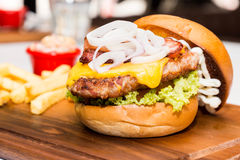 Close up on Pork burger with cheese, vegetable and served with fries Stock Images