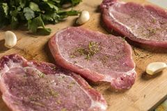 Close up of pork chops on a cutting board with herbs. Close up of pork chops on a cutting board with fresh herbs. Selective focus Royalty Free Stock Image