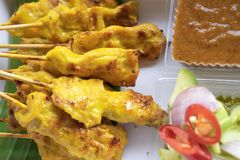 Close up pork satay skewers with peanut dipping suace and sider stock photo