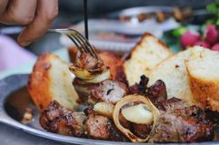 Man`s hand puts a pork shish kebab in a plate royalty free stock image