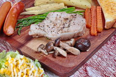 Close up of pork steak and mixed vegetables on butcher served served with side dish .Selective focus. Royalty Free Stock Images