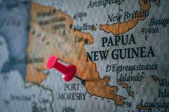 Close up of Port Moresby pin pointed on the world map with a pink pushpin stock images