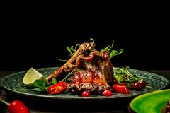 Close up of a portion of barbecued grilled ribs with a in sour sweet berry sauce served with green seedlings on the plate. concept. Of Asian cuisine. restaurant royalty free stock photography