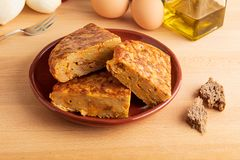 Close-up of portions of homemade Spanish potato omelette with natural ingredients. Fresh eggs, olive oil, potatoes, onion, chorizo royalty free stock photo