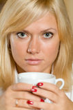 A close-up portpait of a blond with a cup Stock Images