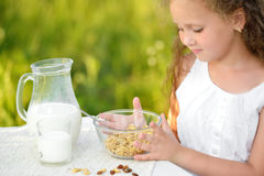 Close up portrait of adorable girl having breakfast and drinking milk outdoor. Cereal, healthy lifestyle. Close up portrait of little girl sitting near the table Royalty Free Stock Images