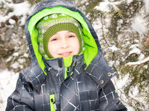 Close up portrait of adorable happy little boy grinning happily at the camera on a sunny winter`s day Stock Photo