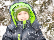 Close up portrait of adorable happy little boy grinning happily at the camera on a sunny winter`s day Royalty Free Stock Images