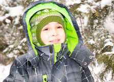 Close up portrait of adorable happy little boy grinning happily at the camera on a sunny winter`s day Royalty Free Stock Image