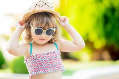 Close-up portrait of adorable little girl at the tropical resort, palm trees at the background, sunny summer day royalty free stock photography