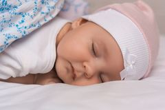 Close up portrait of adorable lovely baby sleeps calmly in bed, covered with warm blanket, has pleasant healthy sweet dream, cared. By affectionate parents Stock Image