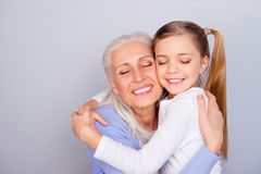 Close up portrait of adorable small lovely sweet charming beautiful girl hugging her careful attentive with white hair granny. Wearing casual clothes on gray stock image