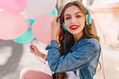 Close-up portrait of adorable smiling girl wearing denim jacket having fun at the birthday party. Stylish young woman