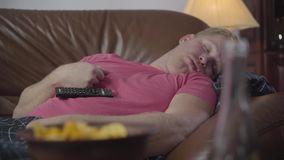 Close-up portrait of adult caucasian man sleeping on couch at home. Lazy guy scratching his face, remote controller