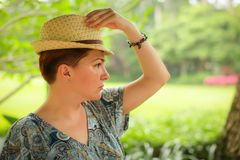 Close up portrait of adult caucasian woman in wicker hat posing with different emotions in green summer park royalty free stock photo