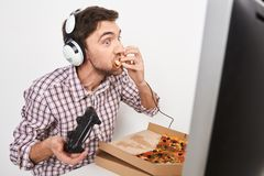 Close up portrait of adult funny male gamer playing online games all day, using controller, talking with team on. Headphones with microphone, sloppily eating Stock Photo