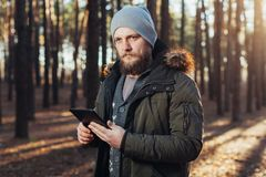 Close up portrait of adult male hiker using digital tab and looking for location during hike in nature. man on hike using digital Royalty Free Stock Images