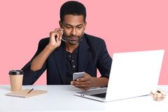 Close up portrait of African American businessman checked email on his smart phone, sits in front of laptop, working online, has stock photos