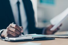Close up portrait of african, american man`s hand writing in org. Anizer, planning his week, holding pencil in workplace, workstation Royalty Free Stock Photos