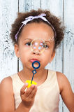 Close-up portrait african  girl blowing soap bubbles Royalty Free Stock Photos