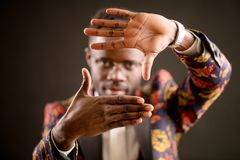 Close up portrait of Africanamerican model making a frame with hands. Close up blurred portrait of Africanamerican model making a frame with hands isolated on royalty free stock photo