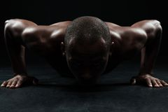 Close-up portrait of afro american sports man, doing pushup exercise. In black interior royalty free stock image