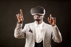 Close up portrait of Afro guy in VR glasses interracting with unreal world. Isolated on the black background. creative world Royalty Free Stock Image