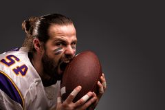 Close up portrait of aggressive American Football Player aggressive player biting his ball.  stock photo