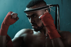 Close-up portrait of aggressive young Muay thai boxer training thai boxing. Action sport concept Stock Photos